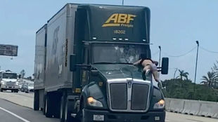Un hombre subido al capó de un camión en una autopista de Florida.