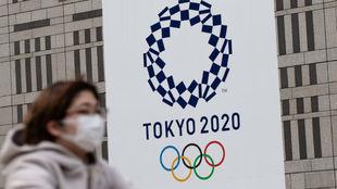 Una mujer pasea con mascarilla delante del logo de los Juegos de...