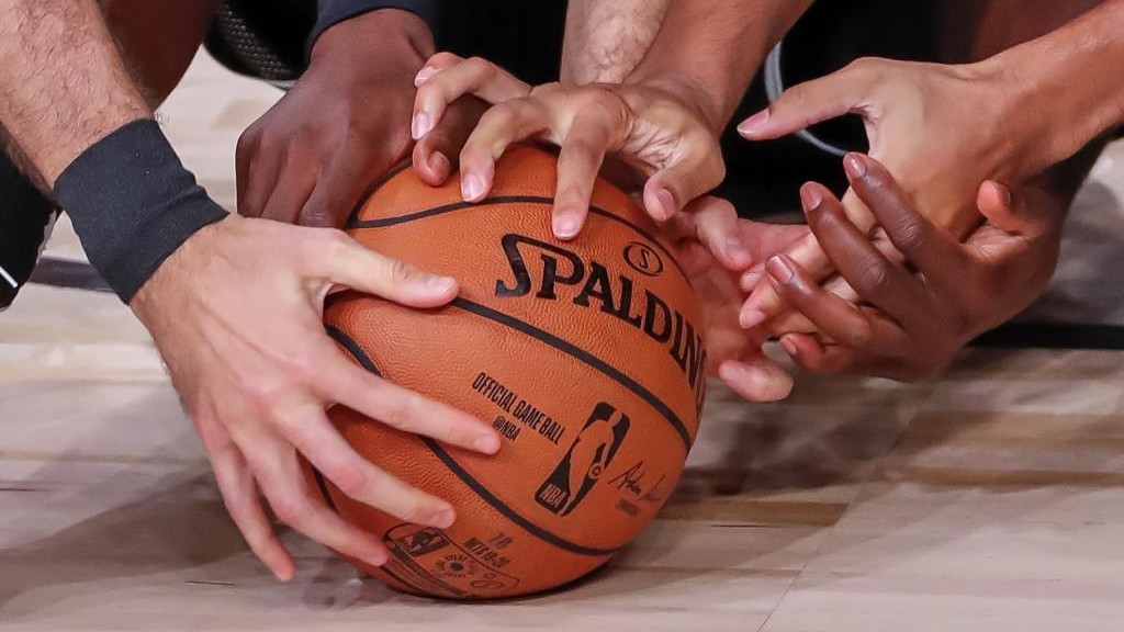 Varios jugadores pelean por un balón suelto durante un partido en la...