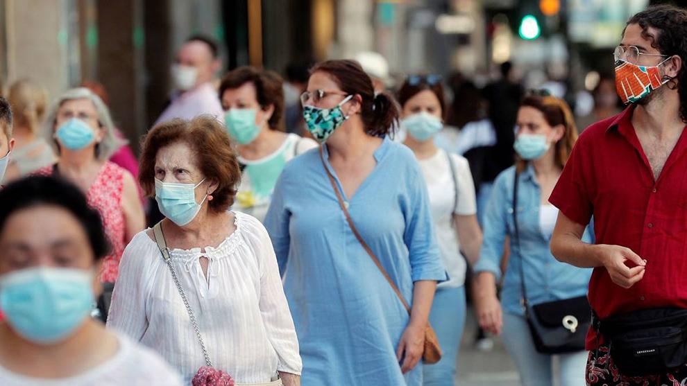 Calle con personas paseando con mascarilla durante la pandemia del...