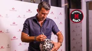 Luis Figo firmando un balón en el 'Santander Media House' de Lisboa.