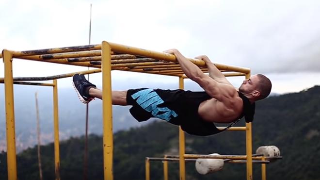 Un hombre practica calistenia al aire libre, aprovechando las barras...