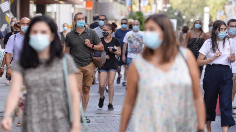 Gente pasea por la calle con la mascarilla puesta.
