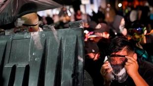 Un manifestante se protege durante una serie de enfrentamientos frente...