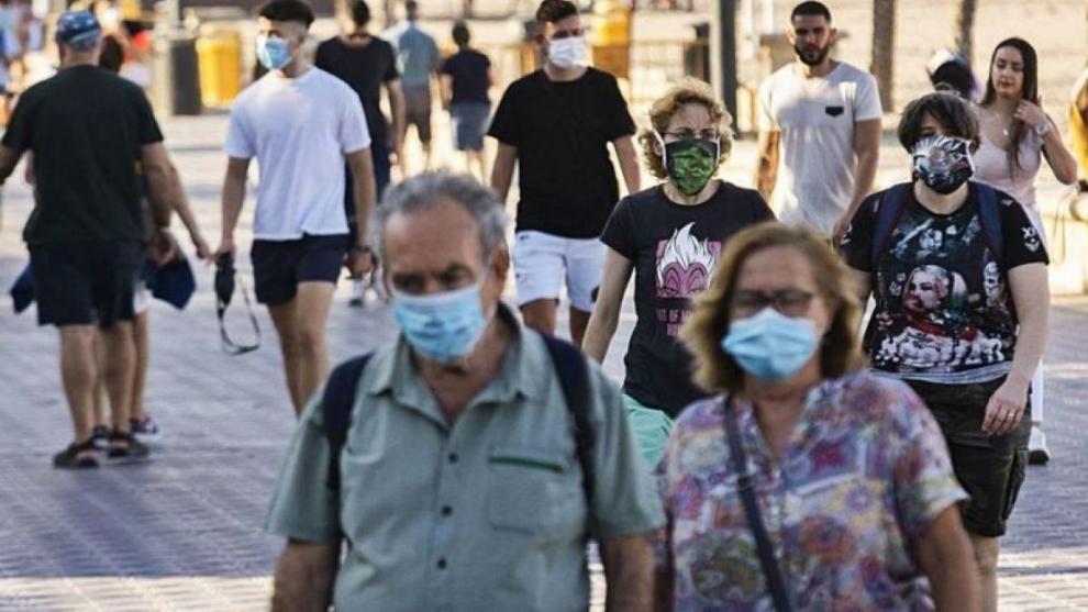 Gente pasea con las mascarillas puestas.