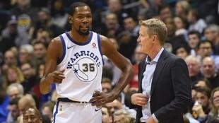 Kevin Duran conversa con Steve Kerr en un partido de los Warriors de...