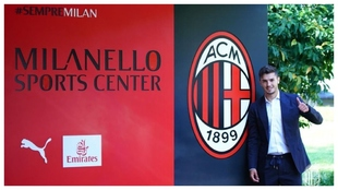 Brahim posa junto al escudo del Milan en las instalaciones deportivas...