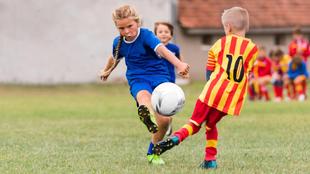 Una niña pugna por el balón con un niño.
