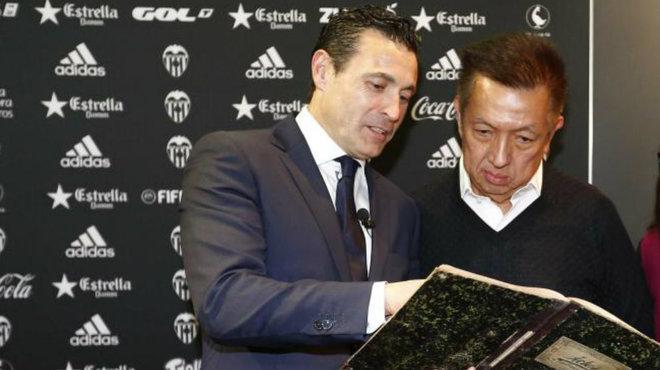Peter Lim repasa un libro de la historia del club junto al...