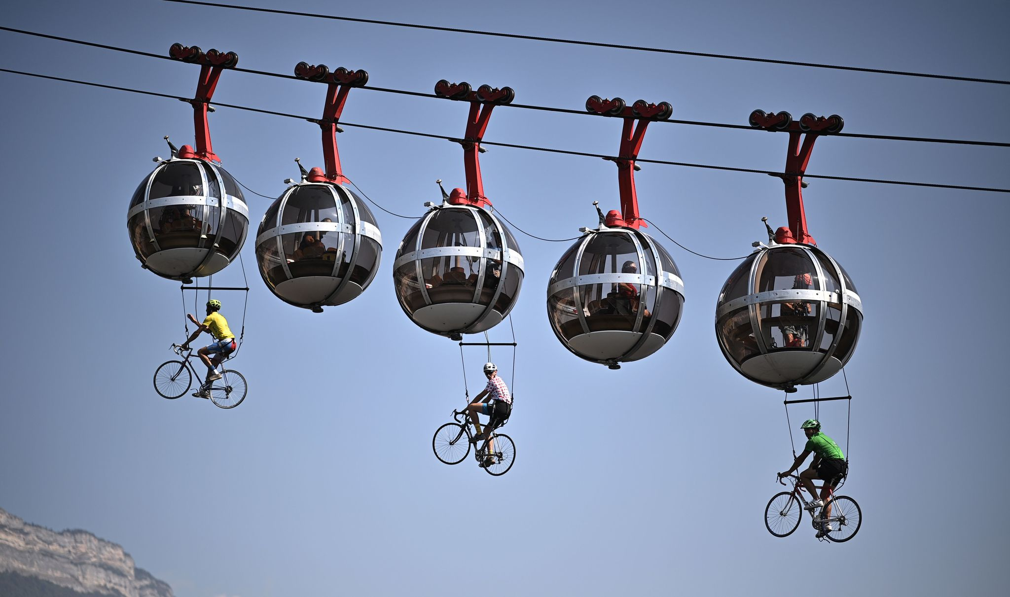 TOPSHOT - This picture shows cyclists hanging under the Grenoble Bastille cable cars during the 17th stage of the 107th edition of the lt;HIT gt;Tour lt;/HIT gt; de France cycling race, 170 km between Grenoble and Meribel, on September 16, 2020. (Photo by Anne-Christine POUJOULAT / AFP)