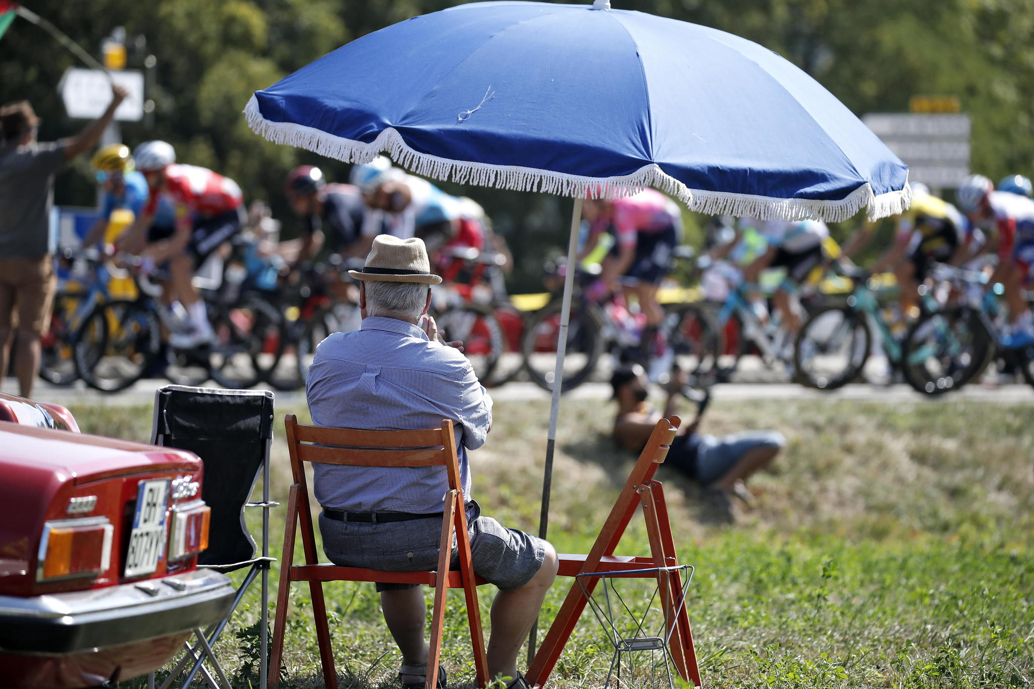 Champagnole (France), 18/09/2020.- A specator sits under a parasol while watching the peloton during the 19th stage of the 107th edition of the lt;HIT gt;Tour lt;/HIT gt; de France cycling race over 166.5km from Bourg-en-Bresse to Champagnole, France, 18 September 2020. (Ciclismo, Francia) EFE/EPA/SEBASTIEN NOGIER