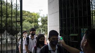 Un profesor mide la temperatura de un alumno en Manaos (Brasil).
