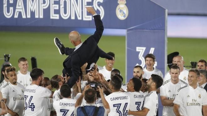 Zinedine Zidane es manteado por sus jugadores en la celebración del...