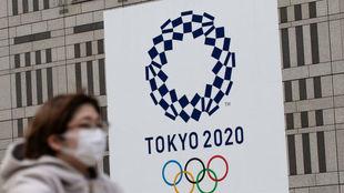 Una mujer con mascarilla pasea delante de un logo de los Juegos de...