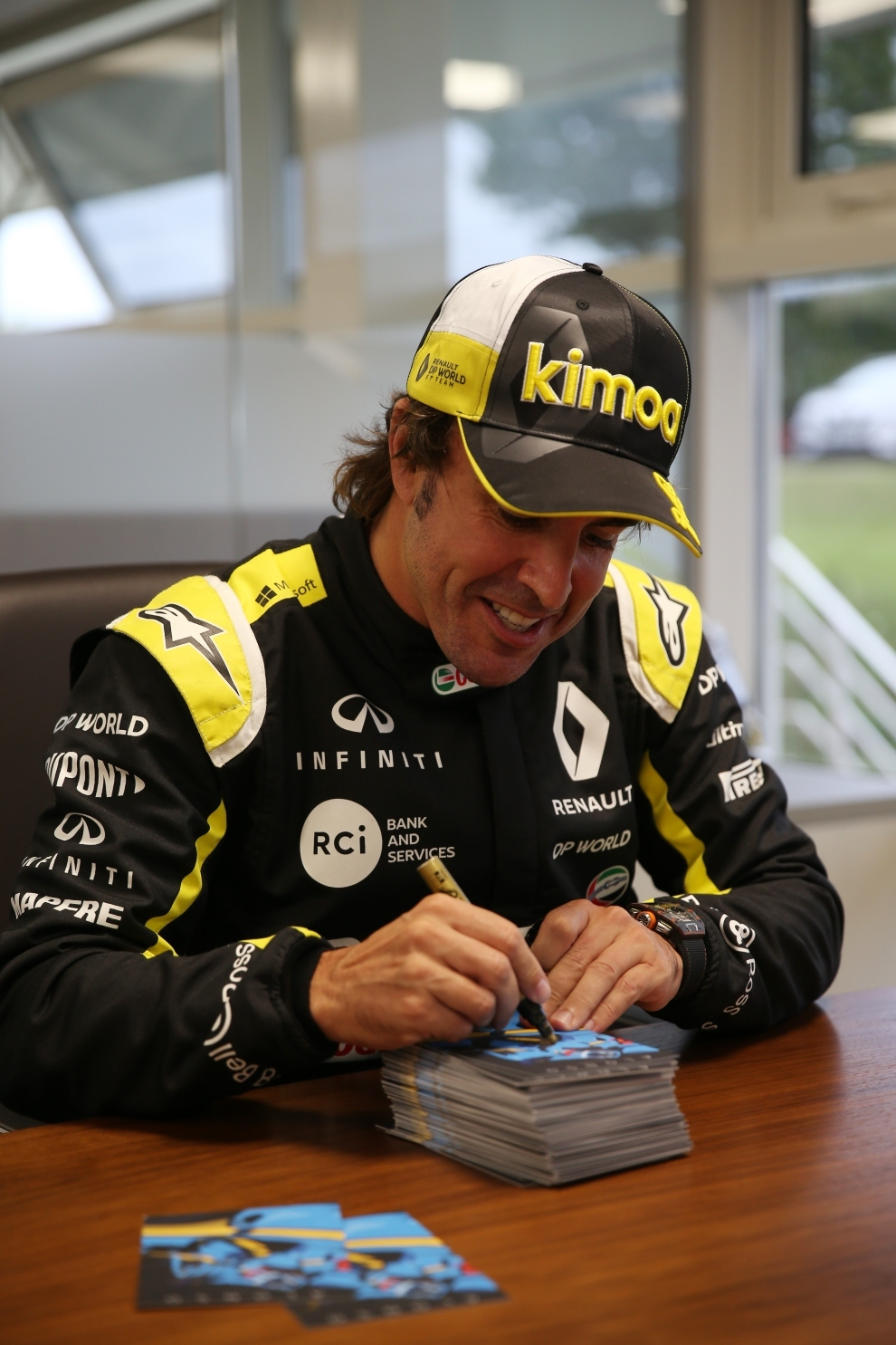 Fernando Alonso firmando fotos.