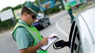Un agente de la Guardia Civil toma nota para multar a un conductor.