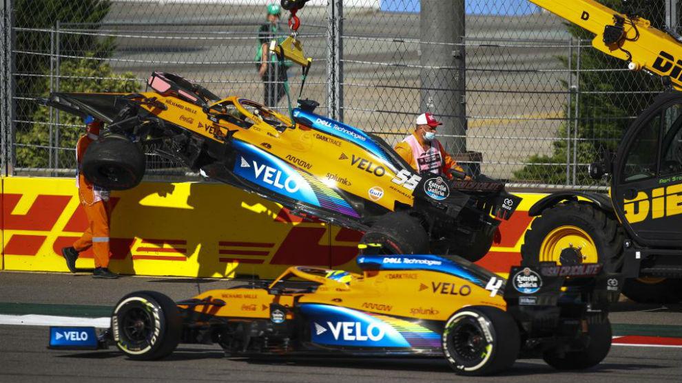 Norris pasa por delante del coche de Sainz, levantado por la grúa en...