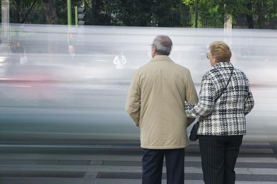 Dos peatones, a punto de cruzar una calle.