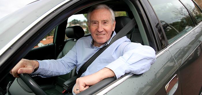 Un hombre mayor conduce su automóvil.
