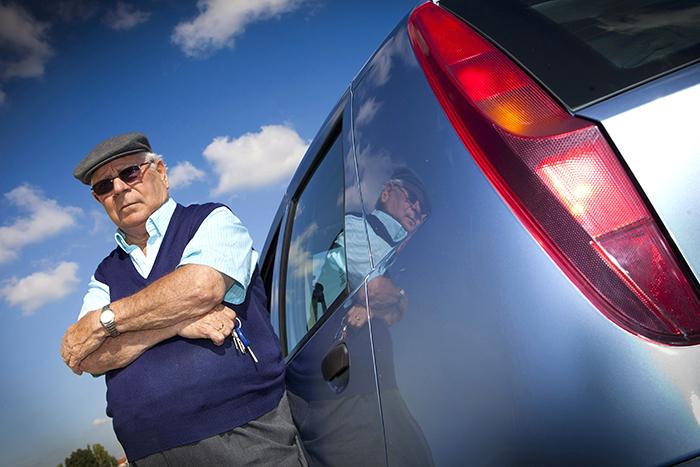 Un hombre mayor, delante de su coche.