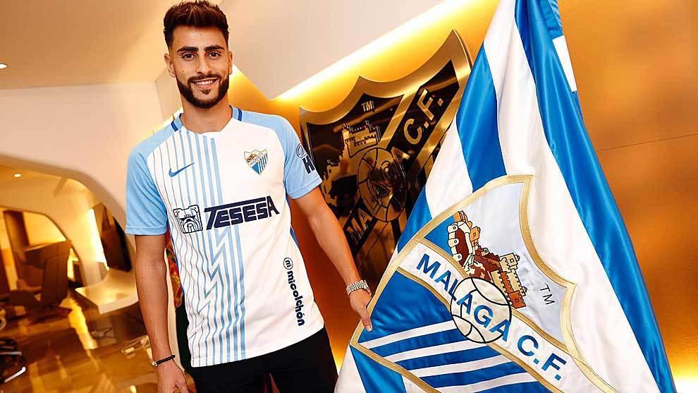 Luis Muñoz posa sonriente junto a la bandera del Málaga