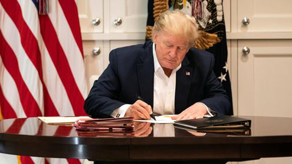 Trump, firmando papeles en el hospital donde está ingresado.