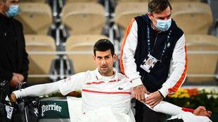 Djokovic siendo atendido del brazo iquierdo