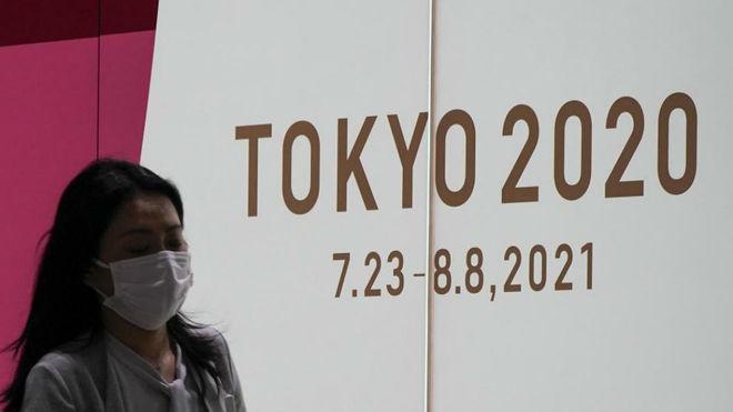 Una persona con mascarilla pasa por delante de un cartel de Tokio...