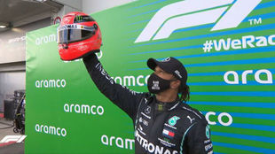 Lewis Hamilton levanta el casco de Michael Schumacher, que le entregó...