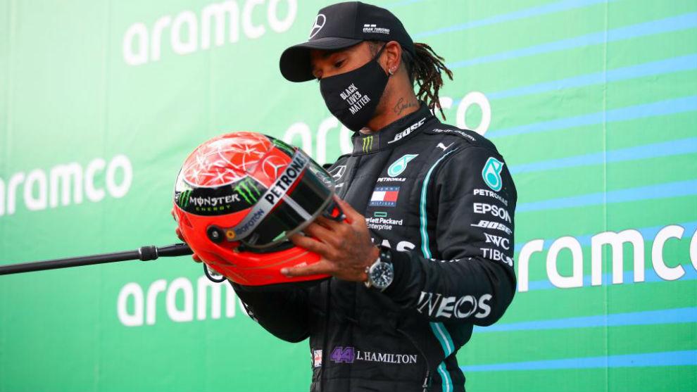 Hamilton, con el casco de Schumacher en el podio de Nurburgring.