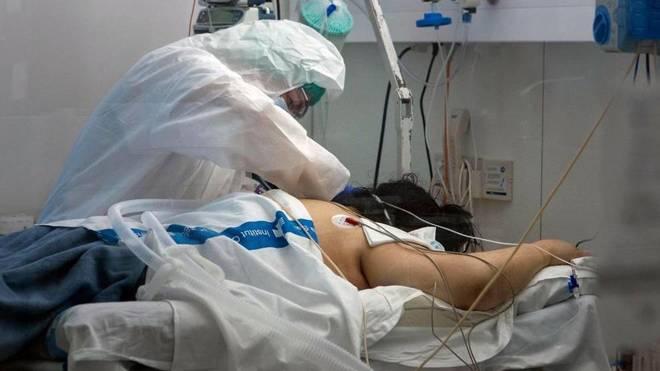 Un sanitario atiende a un paciente ingresado por covid-19