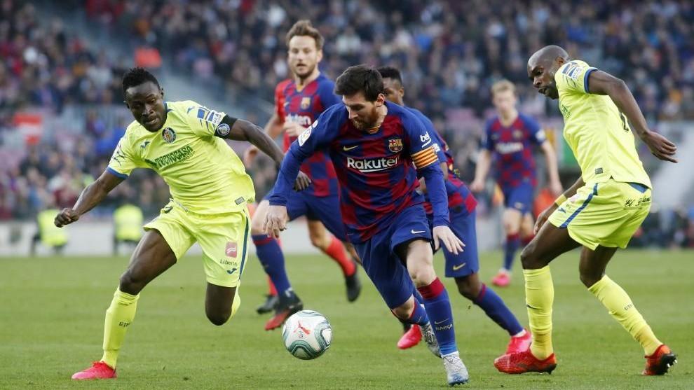Messi, en un partido contra el Getafe rodeado de jugadores.