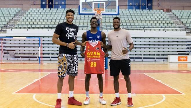 Alex Antetokounmpo posa con la camiseta del ECAM Murcia escoltado por...