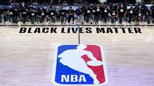 Los miembros de dos equipos de la NBA se arrodillan en el himno antes...