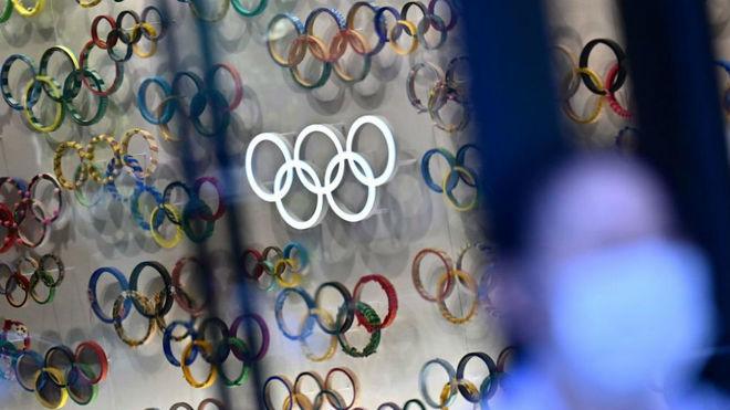 Una persona con mascarilla pasa por delante de varios logos con los aros olímpicos.
