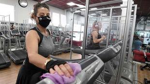 Una usuaria protegida con mascarilla desinfecta una cinta de correr.