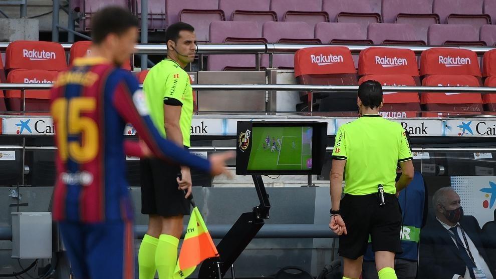 El árbitro, en el momento de examinar la jugada polémica.