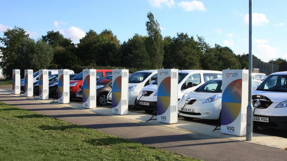 Varios vehículos eléctricos enganchados a puntos de recarga.