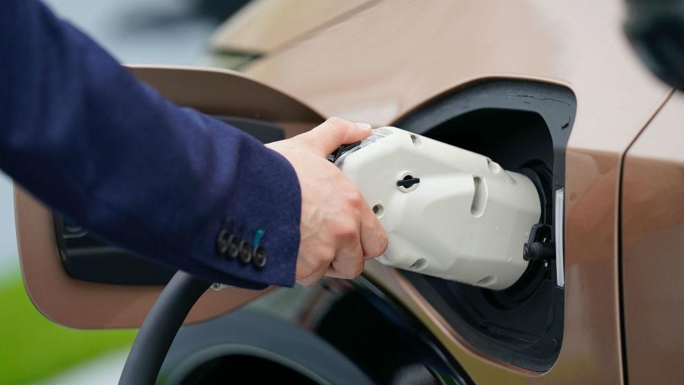 Un hombre enchufa su coche eléctrico para recargar la batería.