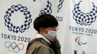 Un joven japonés con mascarilla, delante del logo de Tokio 2020.