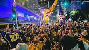 Aficionados de los Lakers celebran el triunfo de su equipo en la final...