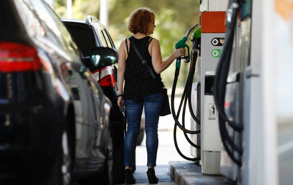 Una conductora retira la manguera de un surtidor para repostar combustible.