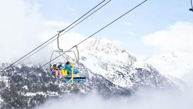Varios esquiadores en un telesilla.