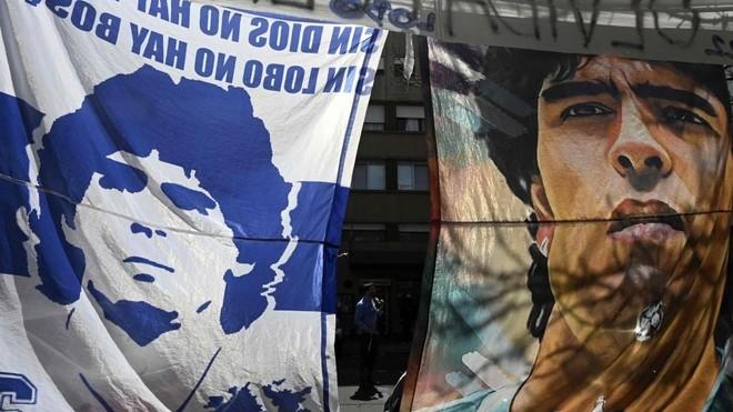 Dos banderas con la imagen de Maradona, colocadas delante de la...
