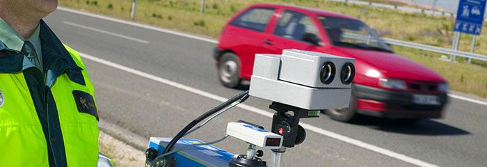 Un agente opera un radar móvil en el margen de una carretera.