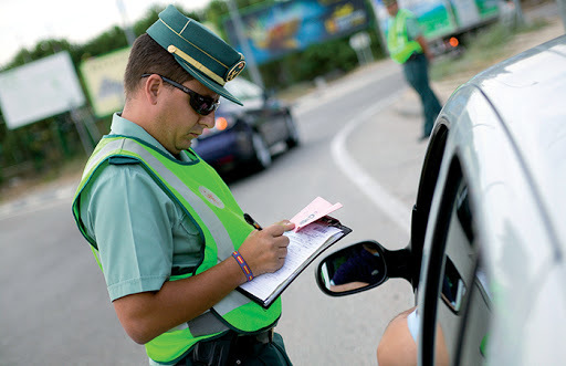 Un agente de la Guardia Civil formaliza una multa a un conductor.