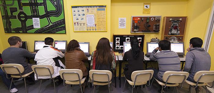 Varios alumnos estudian en una autoescuela.