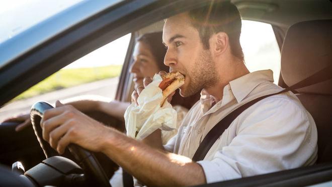 Un conductor se come un bocadillo mientras conduce.