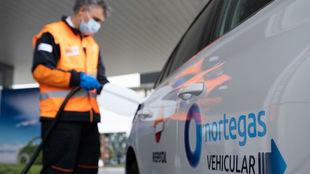 Un expendedor reposta Gas Natural Vehicular (GNV) en un coche.