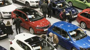 Varios clientes miran coches seminuevos en una feria de vehículos de...